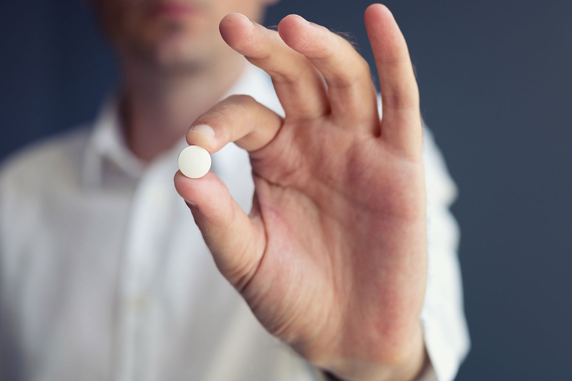 man holding the miracle drug aspirin pill