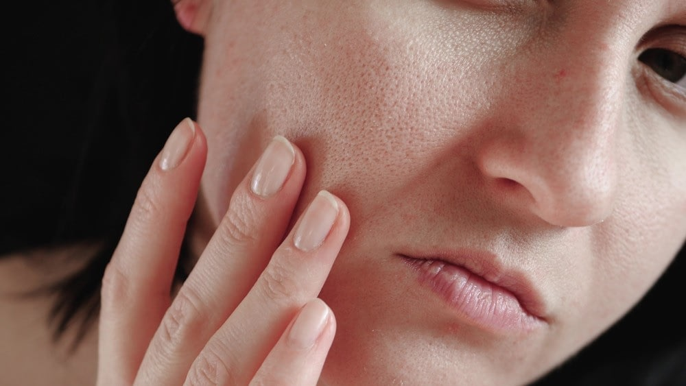 a woman examining her pores to determine her skin type