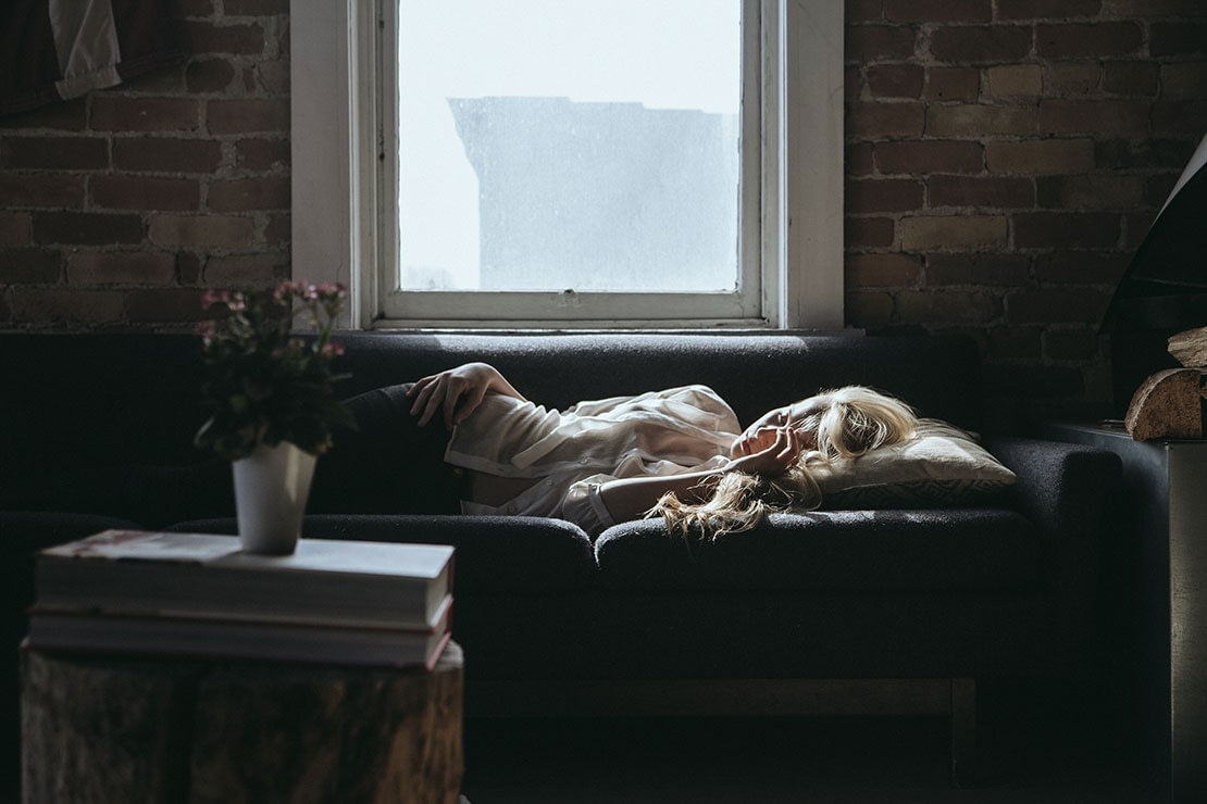 Woman taking a nap on couch next to the window