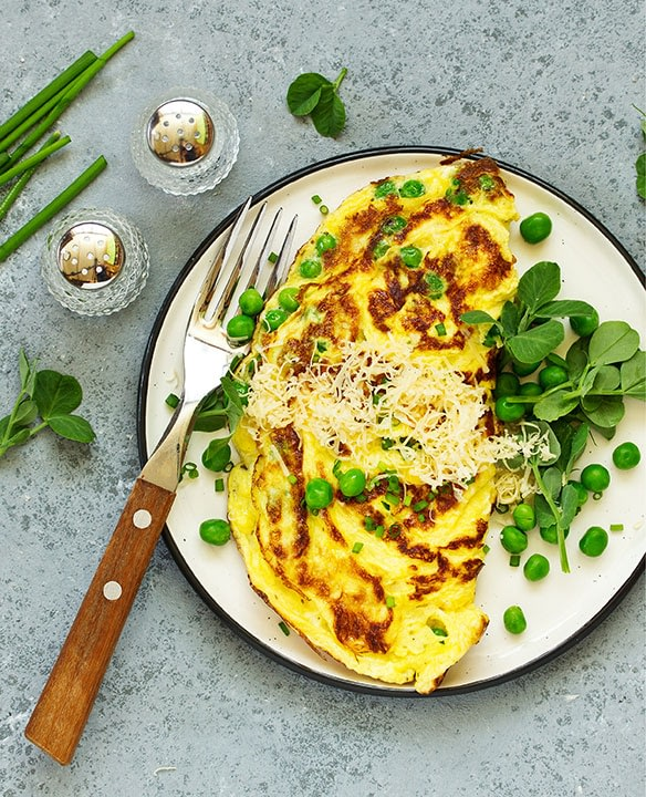 A veggie omelet on a plate with peas and spinach