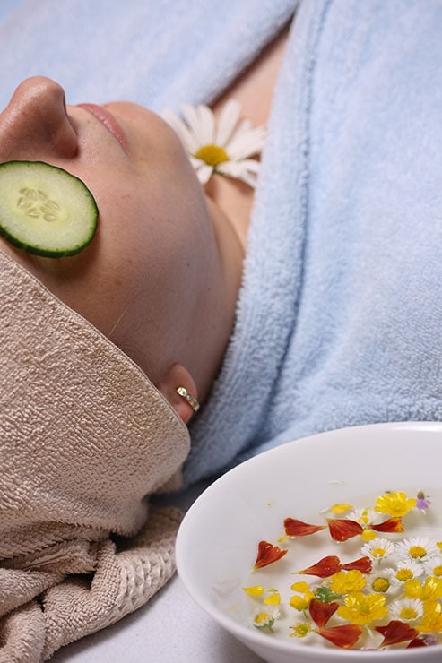 woman receiving spa treatment with cucumber slices over her eyes