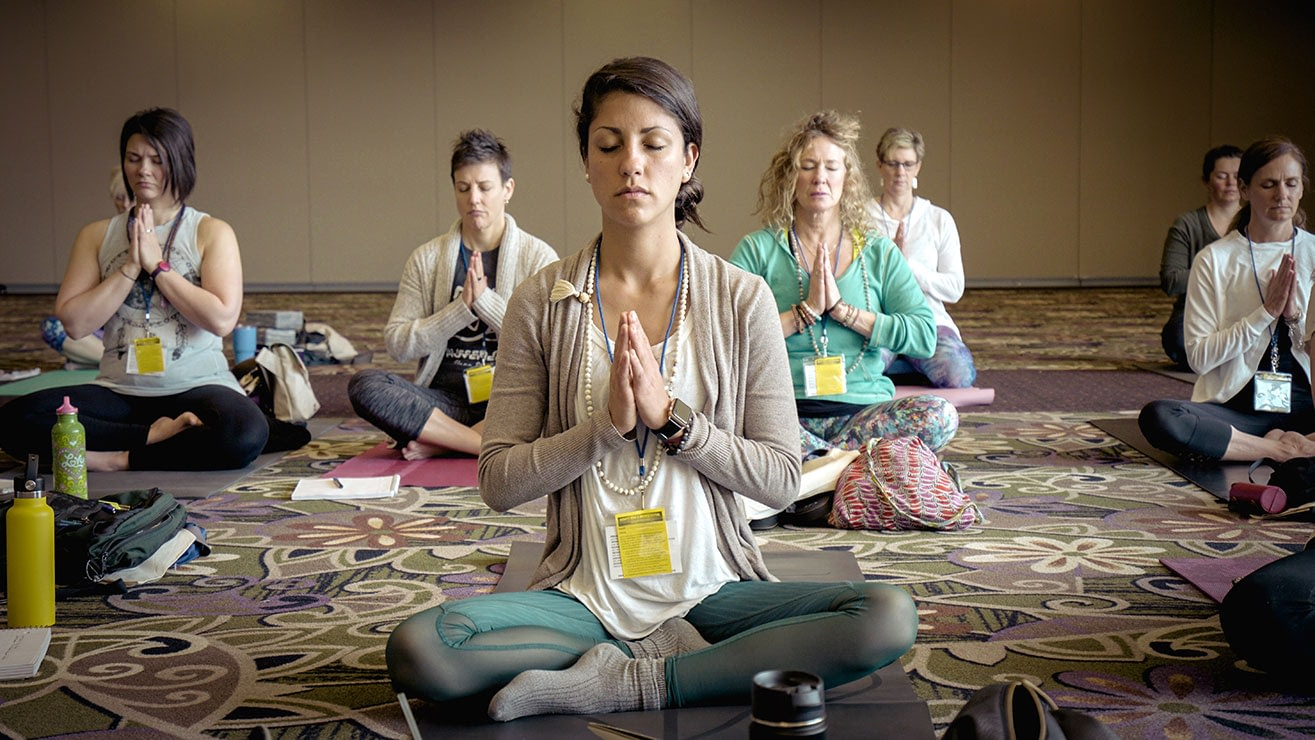 Group of women practicing yoga during a self care retreat