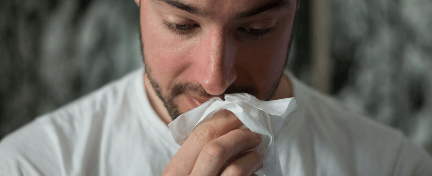 Man holding a tissue up to his nose while looking down