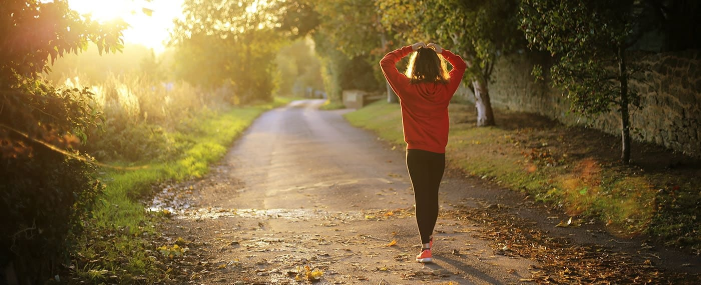 Woman in running gear walking with hands on head through forest path