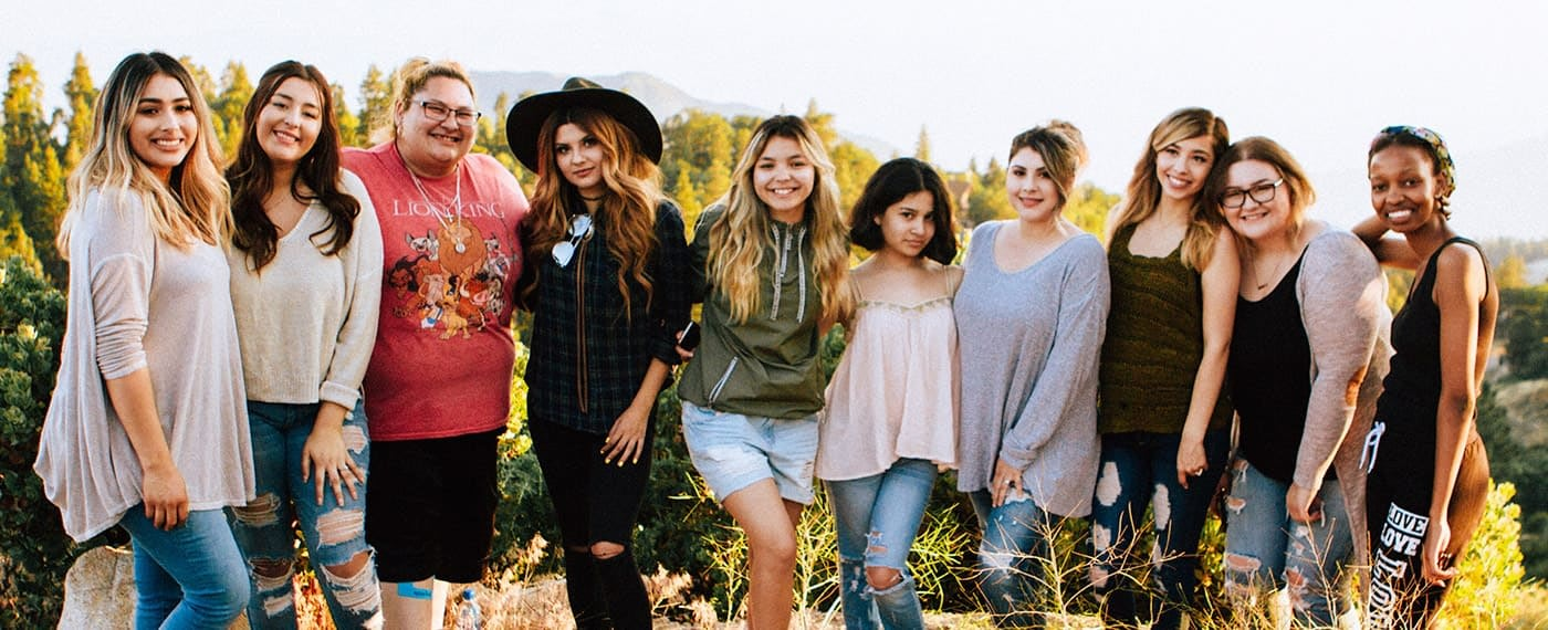 A group of women of different sizes, races, and styles smiling together