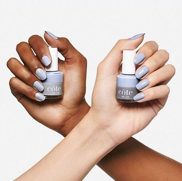 Two different colored female hands holding the Cote nail polish bottle