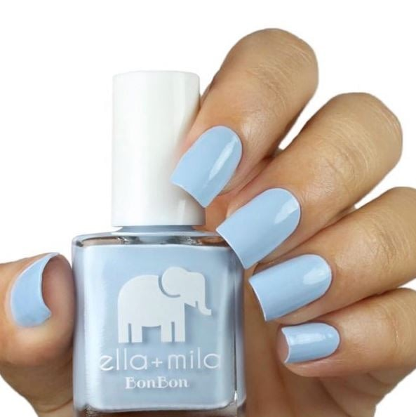 Bright baby blues nails holding a bottle of Ella & Mila Nail Polish