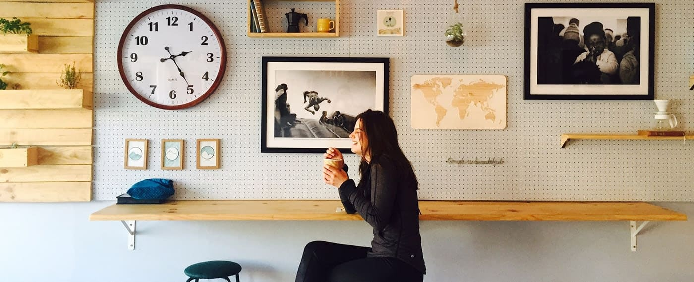 Woman laughing and drinking coffee with framed photos hanging on the walls