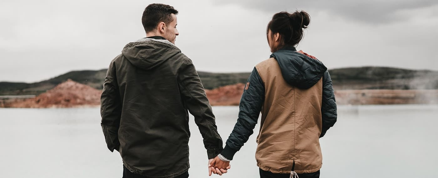 Woman and man in a relationship standing in front of lake holding hands