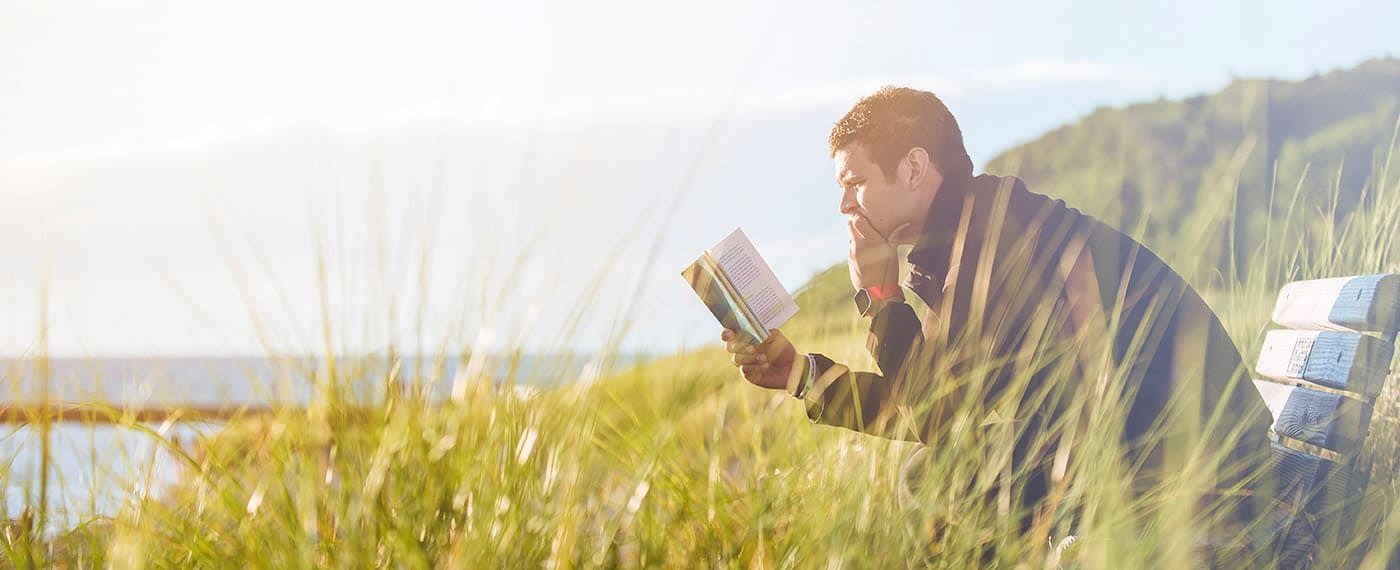 Fit man reading a book while sitting on a bench in a field