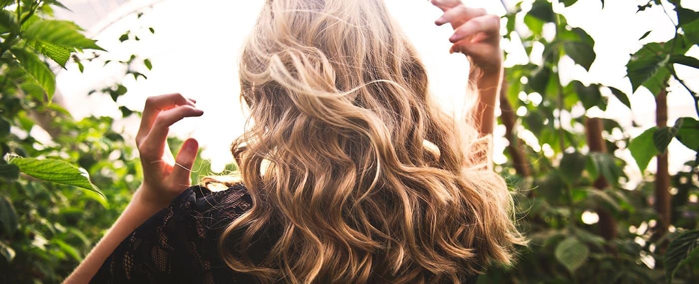 Woman with blonde wavy hair walking through greenery
