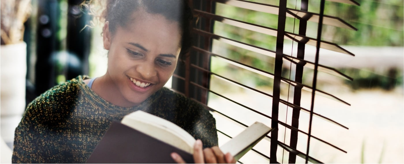 young woman sitting by a sunlit window reading a book about self care