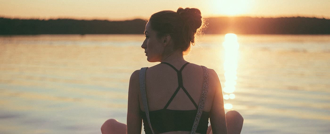 Woman sitting in front of lake looking away from the sunset