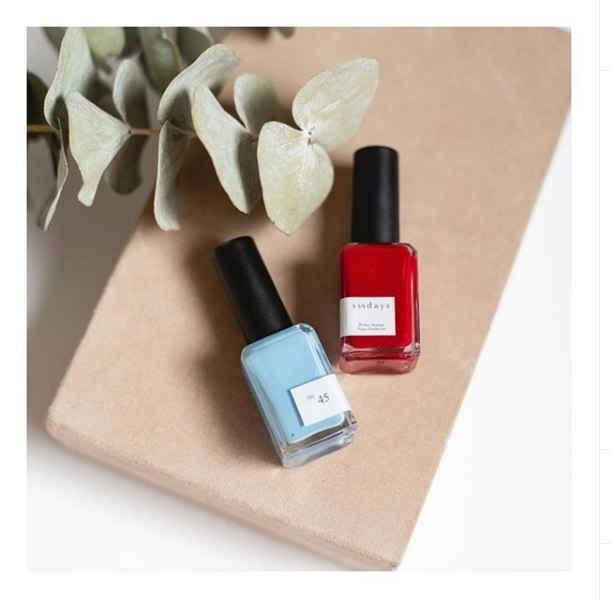 A bottle of baby blue No.45 nail polish next to a bottle of red Sundays Nail Polish