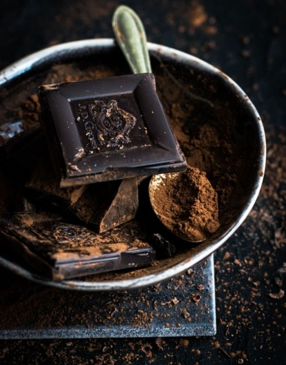 a bowl of dark chocolate pieces and powder rich in antioxidants