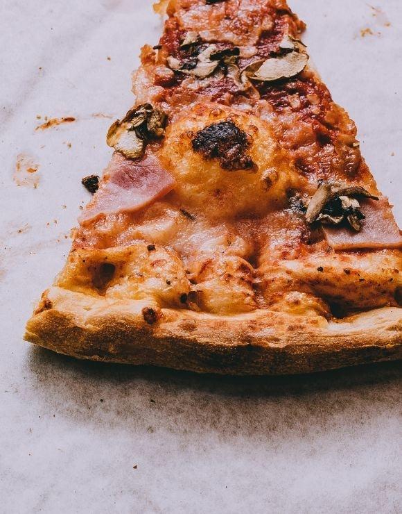 A slice of reheated mushroom and bacon pizza