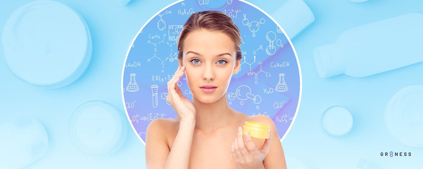 Woman applying skincare product to face while standing in front of chemistry symbols