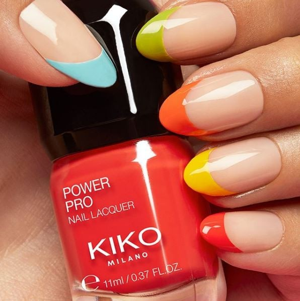 Colorful manicured nails holding a bottle of Kiko Milano Power Pro Nail Lacquer