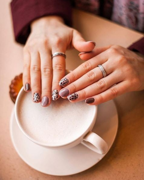 woman showing off trendy manicured nails over coffee mug