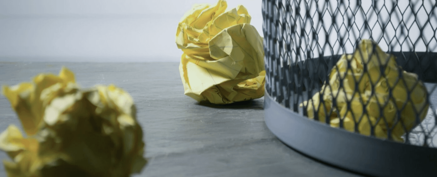 crumpled pieces of paper next to a metal trash bin