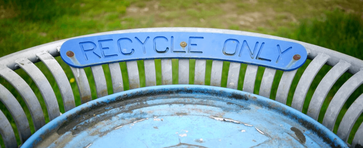 """a rusted trash can with a """"Recycle Only"""" sign"""
