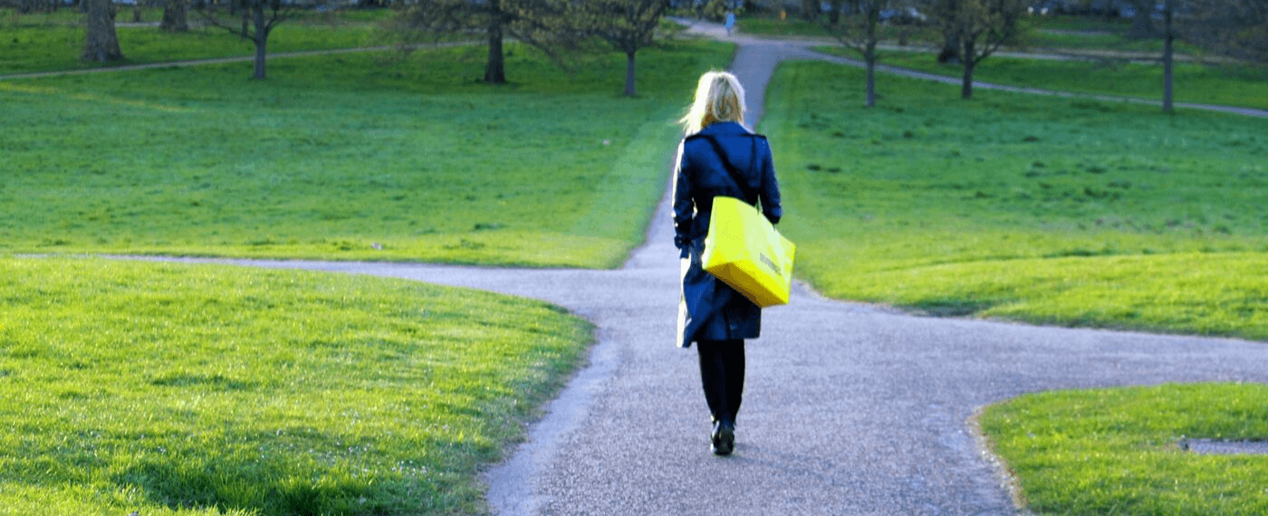 Woman in leather coat walking along a small road path