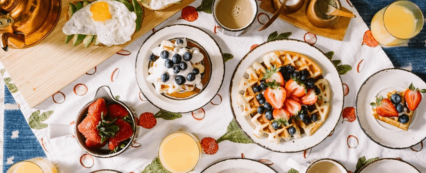 Variety of brunch dishes including waffles, pancakes, strawberries, and juice
