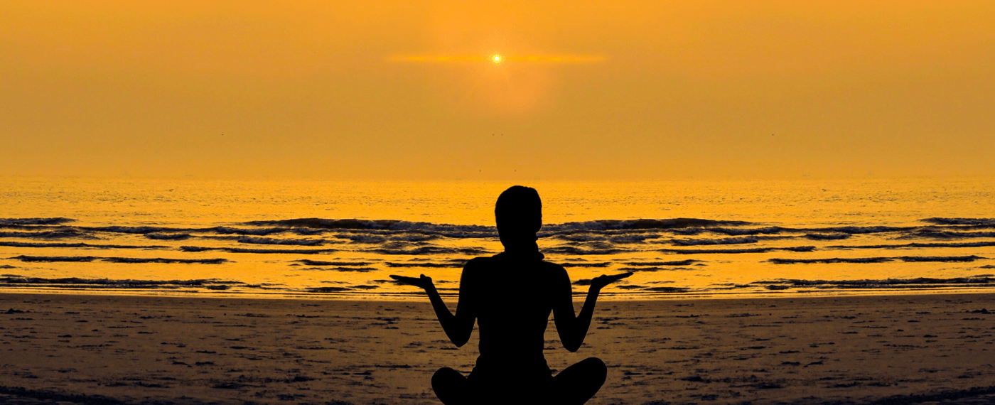 Woman meditating by the beach during sunset