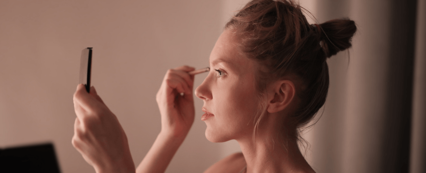 Young woman applying her favorite makeup product to her eyes