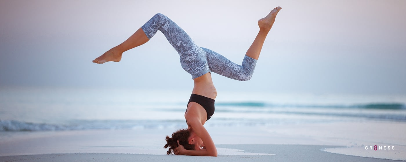 woman balances on top of her head doing yoga on the beach