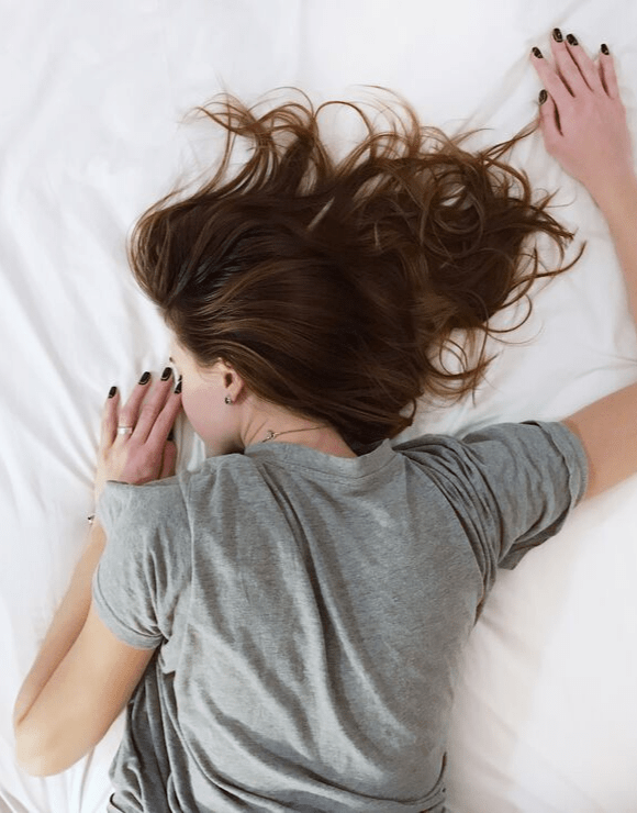 Woman lying restless in bed on her stomach due to unhealthy intermittent fasting