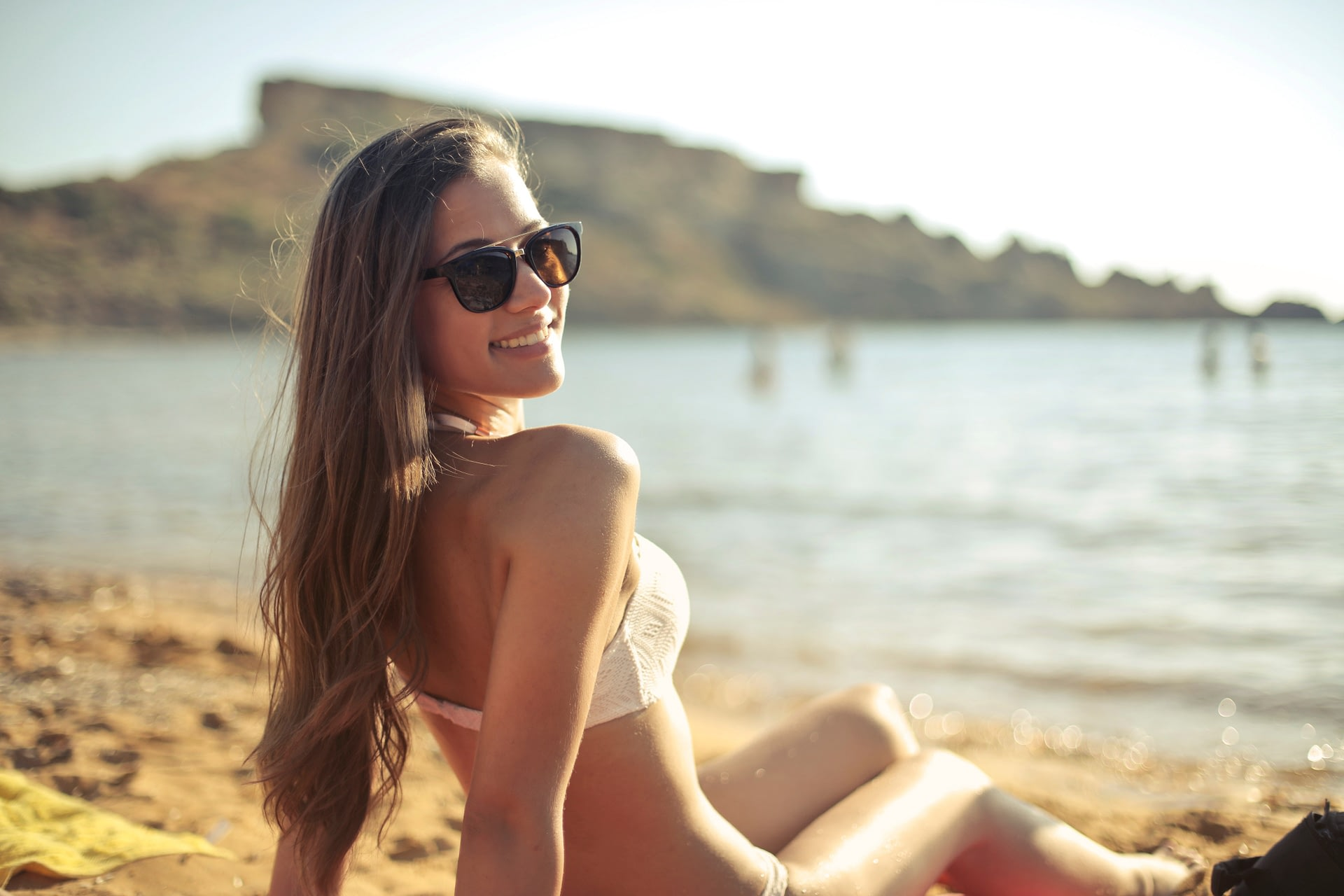 Stylish young girl smiles while tanning on the beach