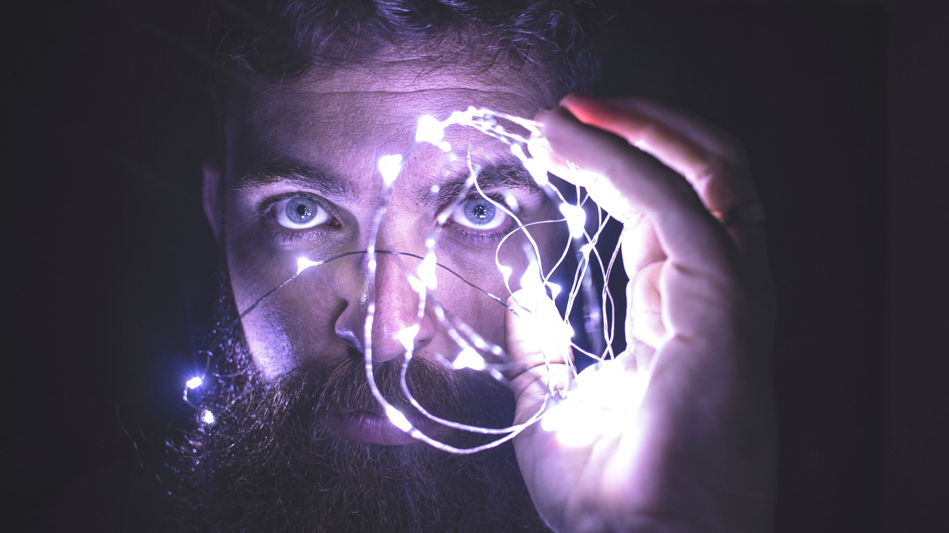 Bearded man holding up a string of led lights near his eyes