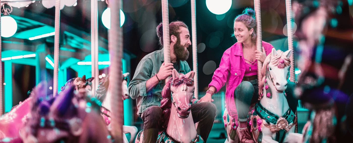 man and woman riding a merry-go-round while holding hands