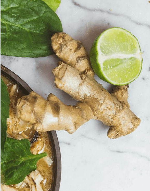 A large piece of ginger with a sliced lime on the side