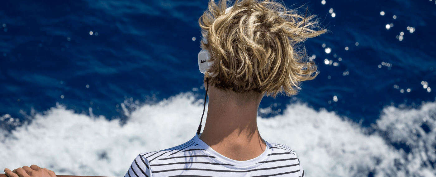 A young man meditates to music while overlooking the balmy sea