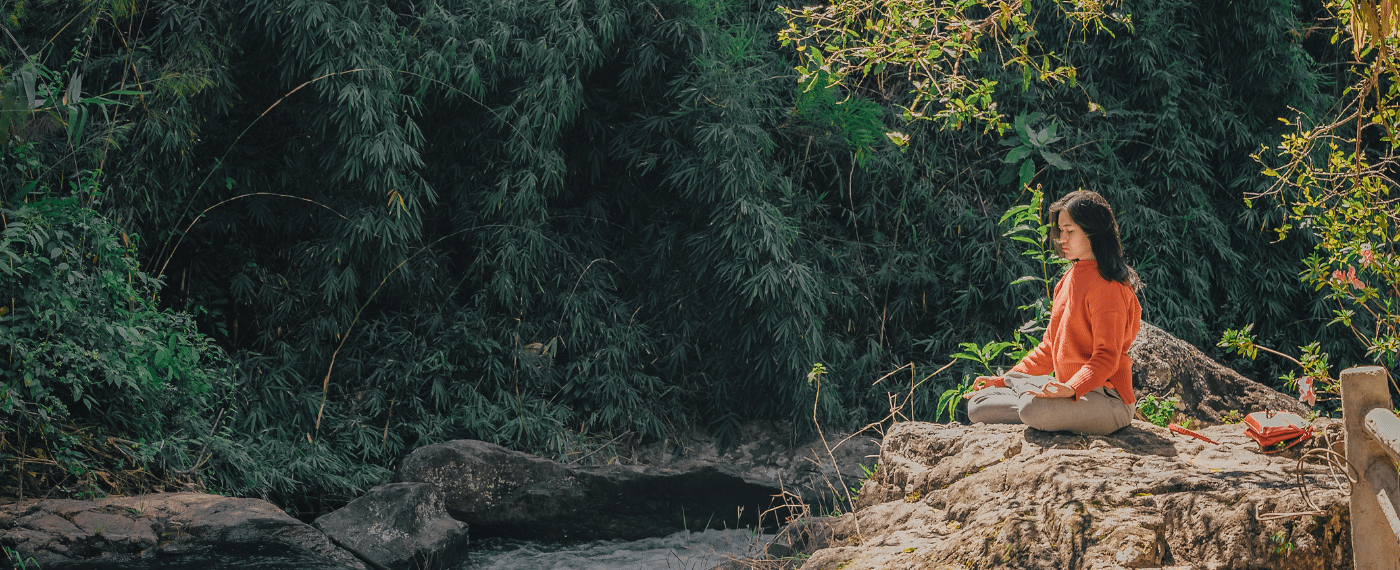 Woman meditating on a rocky ledge next to a flowing river