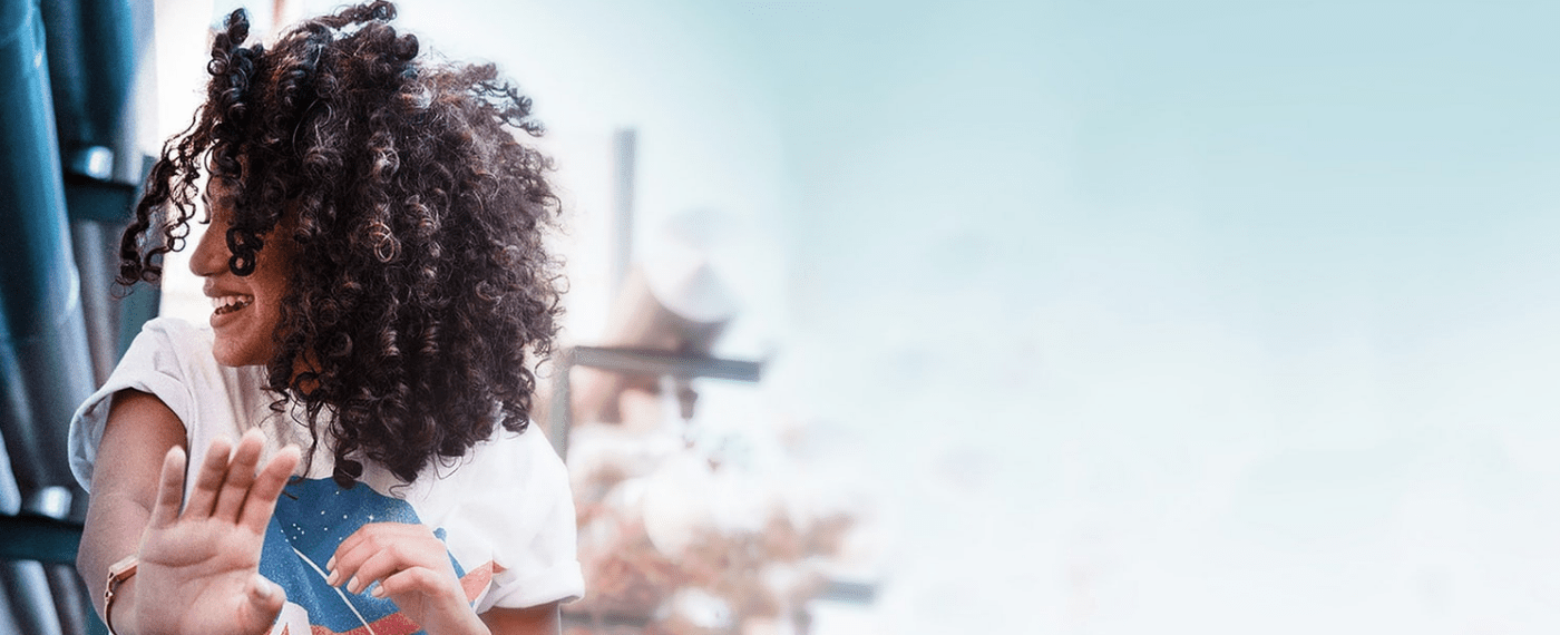 Woman with vibrant curly hair smiling away from camera