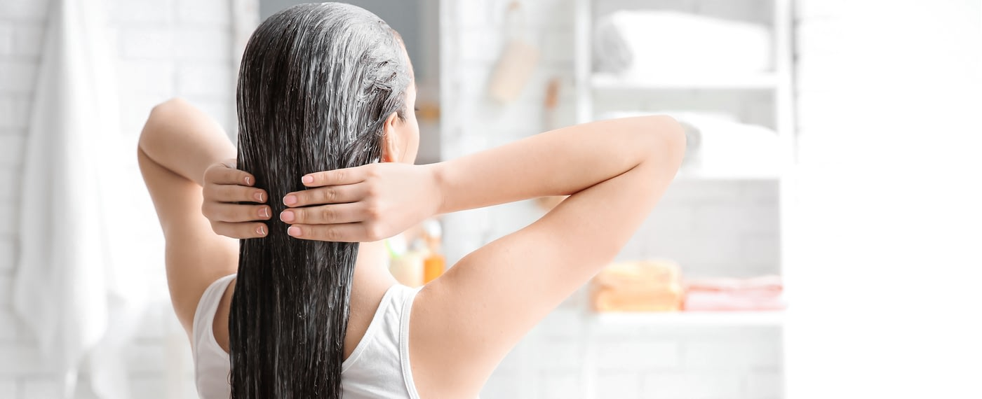 woman gently applying conditioner to her hair