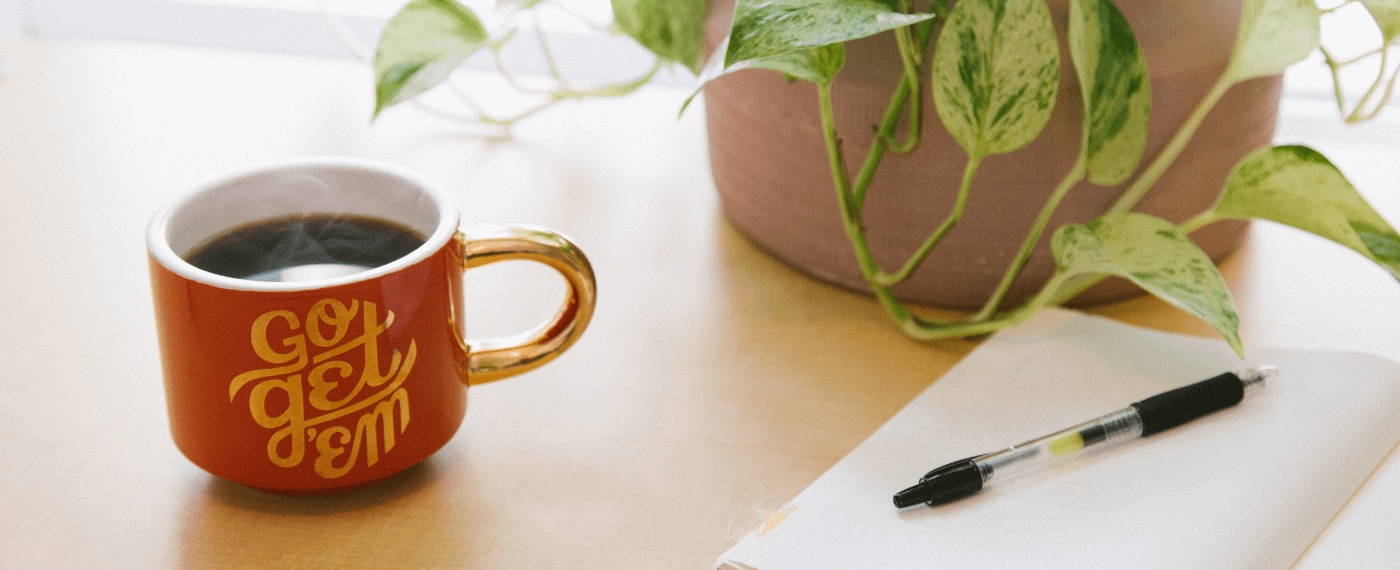 S teaming cup of coffee next to a notepad and pen