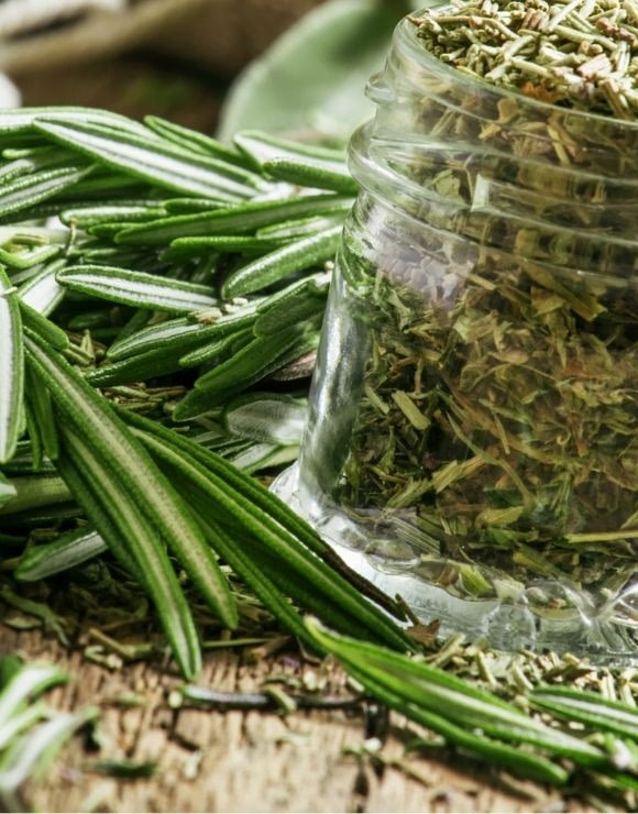 glass jar of ground up rosemary with rosemary leaves on the side