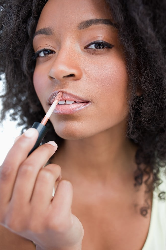 A woman applies lip gloss, unaware of the harmful ingredients inside