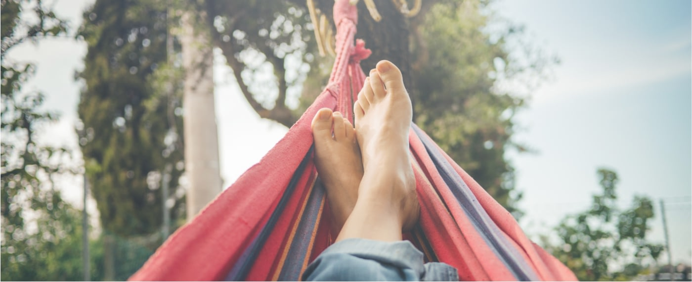 A person taking a mental day to lounge in a hammock