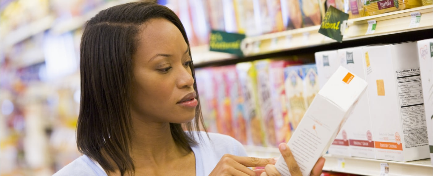 A woman examines the nutrition label on a box of snacks
