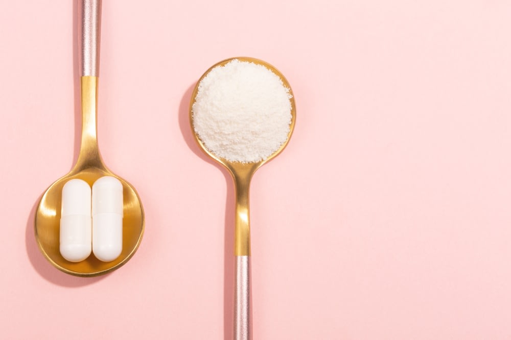 A spoon of capsules next to a spoon of makeup powder