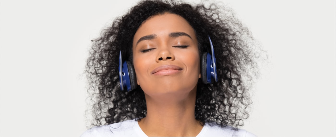 A woman with headphones finds deep relaxation through sound