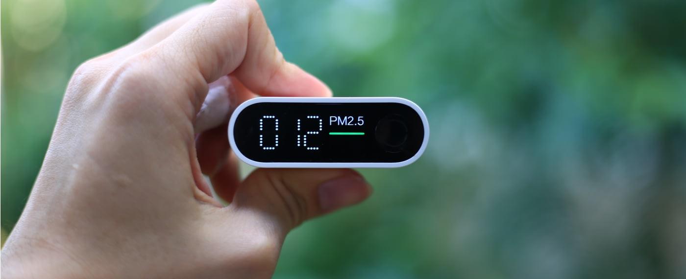 A hand holding a digital air quality monitor