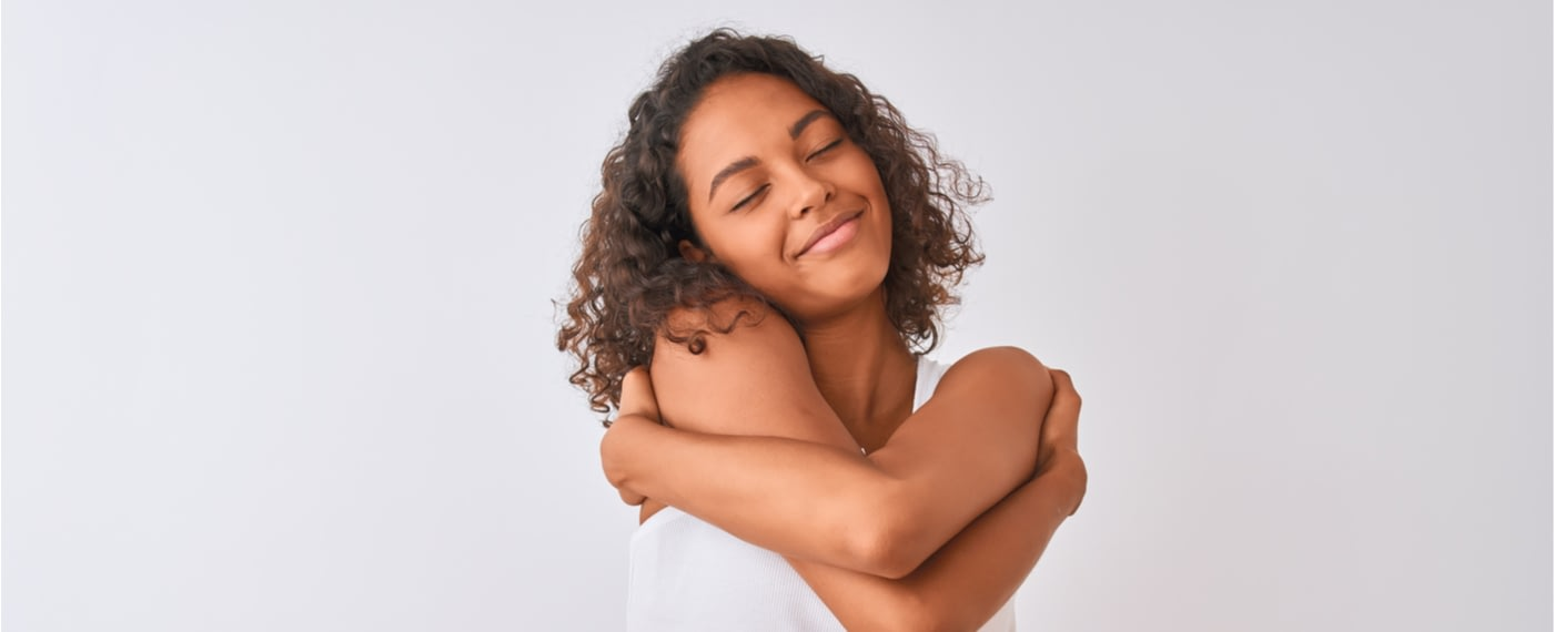 Woman smiling while giving herself a hug