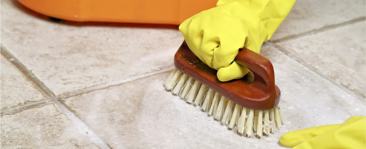 Rubber cleaning gloves using a bristle brush to scrub tile