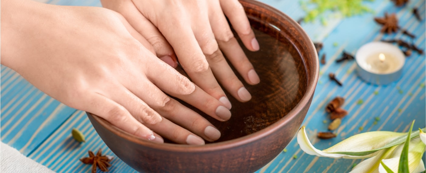 Woman using a small container as a nail care kit